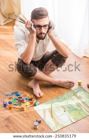 Top view young artist is siting on the floor with paints, palette and brush. - stock photo
