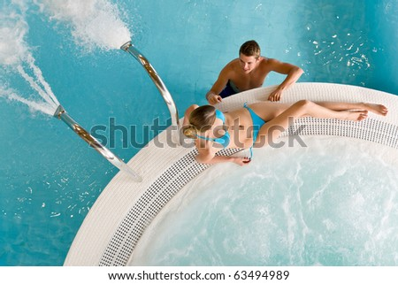 Top view - young couple relax in swimming pool sitting at bubble bath - stock photo