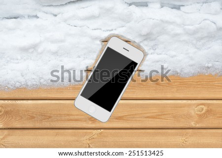 Top white wood office table with smartphone and snow - stock photo