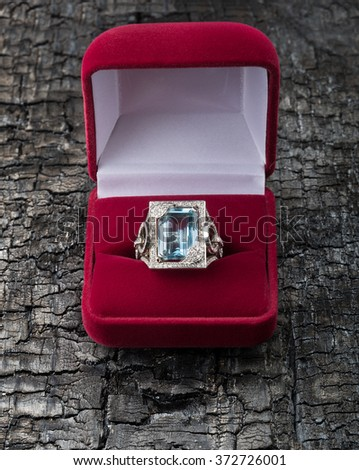 Topaz ring in the open red box on charred board - stock photo