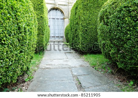 Topiary Hedgerow Lined Garden Path Leading to an Old English Country House - stock photo