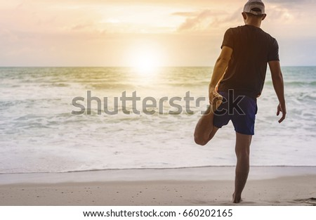 Topical beach with young man standing against sunset in the sea,he is going to swim,summer vacation concept