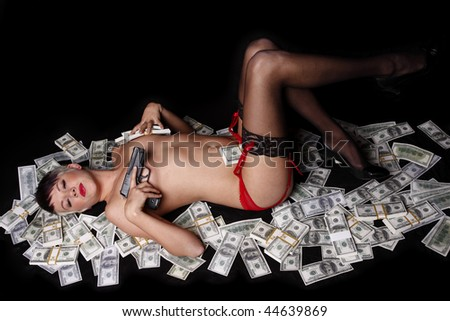 Topless and sexy woman in lingerie laying on cash with a gun.