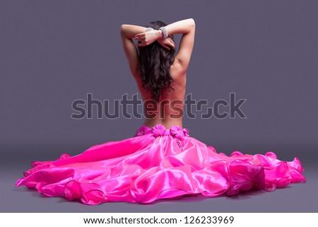 topless dancer in pink costume sitting on floor - stock photo