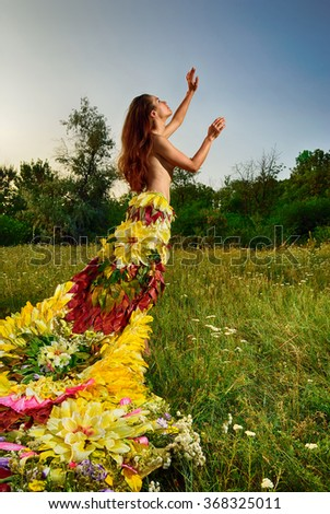 Topless girl in a dress made of flowers - stock photo