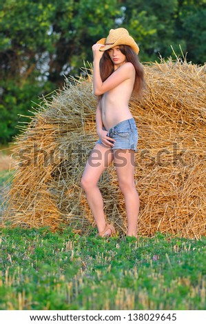 Topless girl in a hat in the hayloft - stock photo