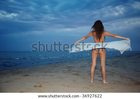 Topless lady at the sea covered by towel - stock photo