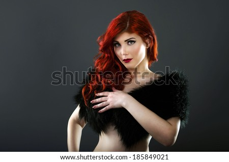 Topless redhead covering her breasts with a black fur coat