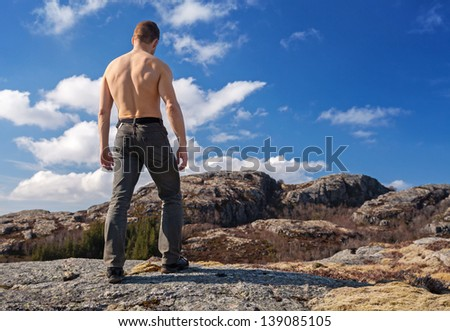 Topless strong man stands on the mountain and looks down - stock photo