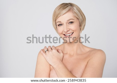 Topless woman covering her chest with hands - stock photo