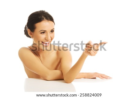 Topless woman sitting at the desk and pointing to the right.