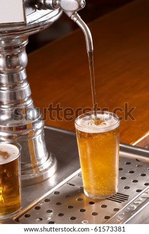 Topping up pint glasses from the draft - stock photo
