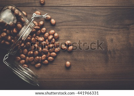 topple over glass jar full of chocolate sweets background - stock photo