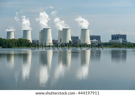 Tops of cooling towers of thermal power plant and reflection in water.