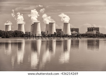Tops of cooling towers of thermal power plant and reflection in water. /White balance changed/ - stock photo