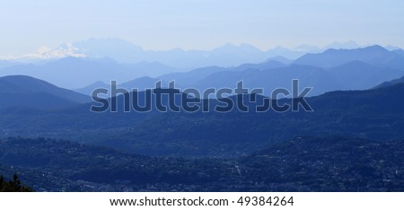Tops of mountains in the mist, photographed from the valley of Intelvi. background Monte Rosa