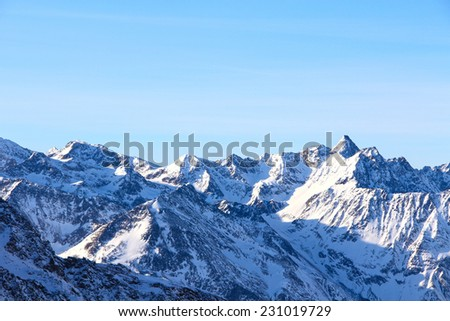 Tops of winter alp mountains at sunny day