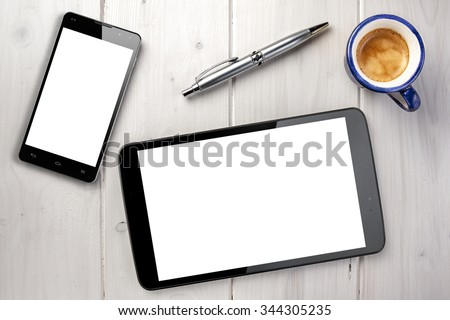Topview modern tablet smartphone with blank screen cup of coffee and silver ballpoint on white wooden table