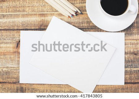 Topview of antique wooden table with blank envelopes, coffee cup and pencils. Mock up