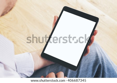 Topview of blank tablet in male hands on wooden background. Mock up