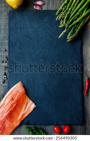 Topview of delicious salmon fillet with asparagus and aromatic herbs, spices and vegetables - healthy food, diet or cooking concept. Copyspace. - stock photo