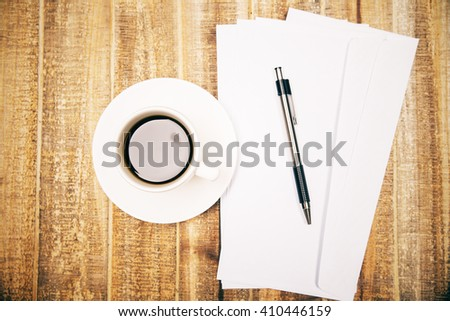 Topview of wooden desktop with white coffee cup, blank envelopes and pen