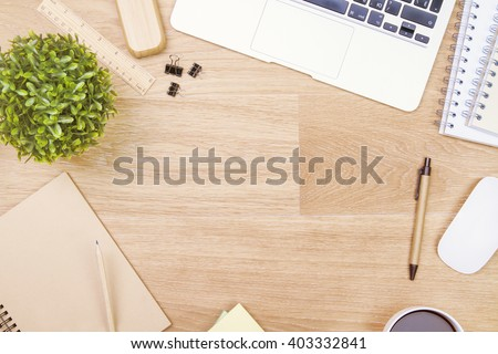 Topview of wooden table with office tools and plant. Mock up - stock photo