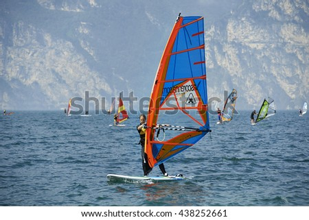 Torbole - Nago, Italy - August 12, 2015: Windsurfers surf on the lake in summer. Windsurfing water sport on Lake Garda. Dolomites mountains background. Italy.