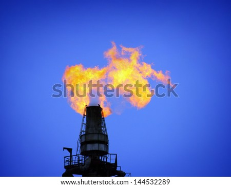 torch is lit on tower refinery - air pollution - stock photo