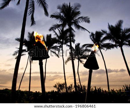 Torches light the evening on the beach in Wailea on Maui - stock photo