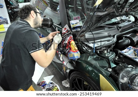 TORINO, ITALY - FEBRUARY 15, 2015: Car wrapping specialist wraps a sportive tuned car parts with colored adhesive foil or film using a squeegee at Expo Tuning Torino on February 15, 2015 - stock photo