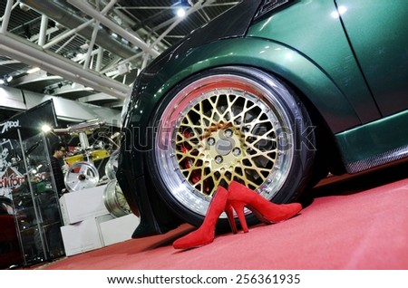 TORINO, ITALY - FEBRUARY 15, 2015: Composition of very big and special sportive car rim in gold near a pair of red high heels shoes at Expo Tuning Torino on February 15, 2015 - stock photo