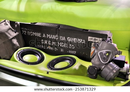 TORINO, ITALY - FEBRUARY 15, 2015: Rear view of car with peronalized open trunk. Military bomb and gas mask inside a car trunk with car power audio system at Expo Tuning Torino on February 15, 2015 - stock photo