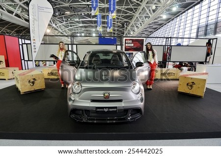 TORINO, ITALY - FEBRUARY 15, 2015: Two sensual and beautiful models for the new Fiat 500 Abarth 695 Biposto edition poses at the Expo Tuning Torino show room car business place on February 15, 2015 - stock photo