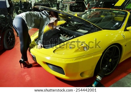 TORINO, ITALY - FEBRUARY 15, 2015: Yellow Ferrari 360 spider F1 tuned version with sensual and young female model with high heels inspecting car engine at Expo Tuning Torino on February 15, 2015 - stock photo