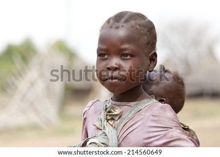 TORIT, SOUTH SUDAN-FEBRUARY 21 2013: An unidentified little girl responsible for carrying her baby sister in Torit, South Sudan - stock photo