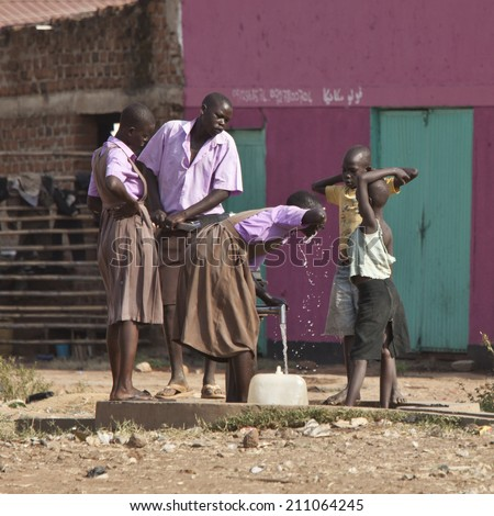 TORIT, SOUTH SUDAN-FEBRUARY 20 2013: Unidentified students drink from a well in the town of Torit, South Sudan - stock photo