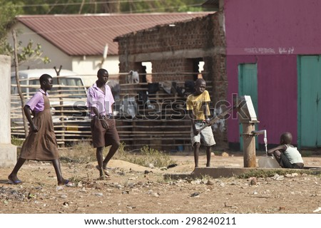 TORIT, SOUTH SUDAN-FEBRUARY 20, 2013: Unidentified students walk past two children at a a public water well in Torit, South Sudan - stock photo