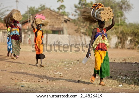 TORIT, SOUTH SUDAN-FEBRUARY 20 2013: Unidentified women carry heavy load on their heads in Torit, South Sudan. - stock photo