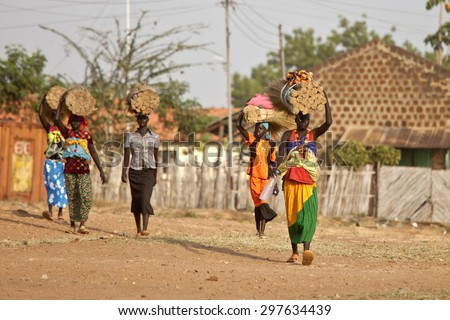 TORIT, SOUTH SUDAN-FEBRUARY 20, 2013: Unidentified women carry heavy loads on their heads in the village of Torit, South Sudan - stock photo
