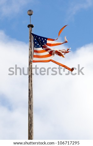 Torn American flag flying from a rusty pole.  Shot against a blue sky with clouds. - stock photo