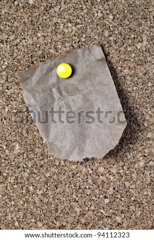 Torn and wrinkled piece of brown paper grocery bag attached to corkboard with yellow pin ready for your message