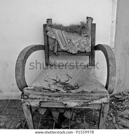 Torn armchair and pile of broken glass. Black and white. - stock photo