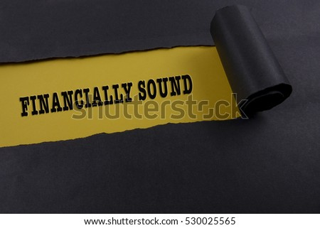"Torn black paper on yellow surface with ""financially sound"" word. Business concept"