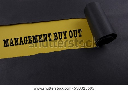 "Torn black paper on yellow surface with ""management buy out"" word. Business concept"