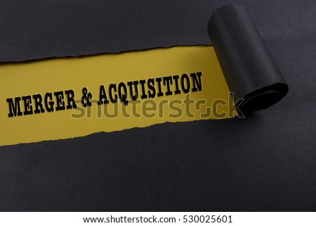 "Torn black paper on yellow surface with ""merger & acquisition"" word. Business concept"