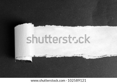 Torn black paper  with brown background - stock photo