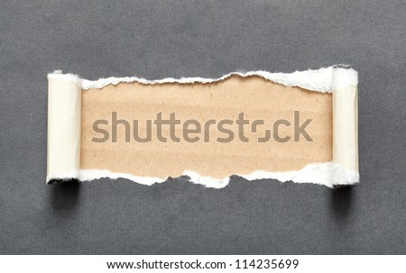 Torn black sheet of paper with beige space for your message - stock photo