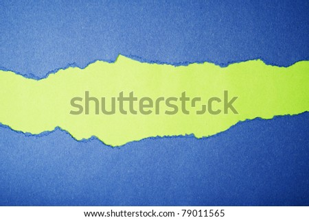Torn blue color paper on green color paper background with space for text - stock photo