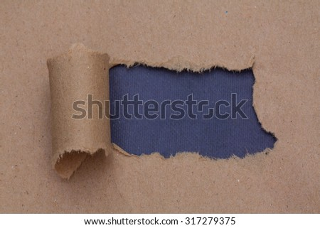Torn brown color paper with space for text with blue background - stock photo
